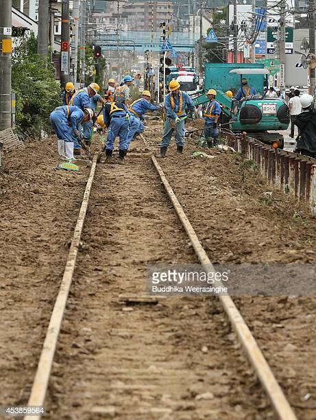 A rail track is repaired by workers after it was destroyed by a landslide caused by torrential rain at the site of a landslide in a residential area...