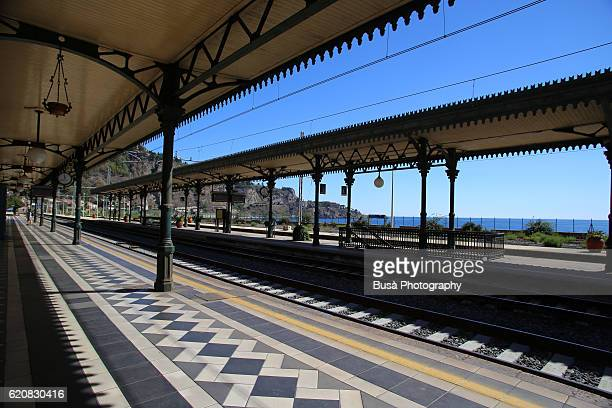 Rail tracks and art-nouveau ornate platform roofs in the Station of Taormina, Sicily, Italy