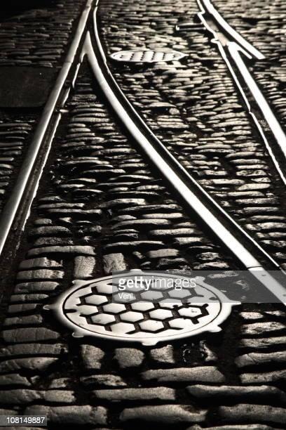 Rail tracks and manholes on cobblestone street 2