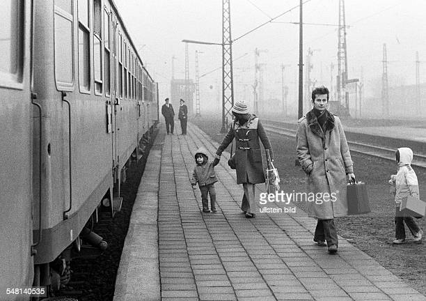rail traffic main railroad station Bottrop young family with two children dismounted the train and walks along the platform to the station exit aged...