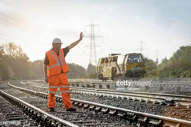 Rail worker signalling to maintenance train on railway