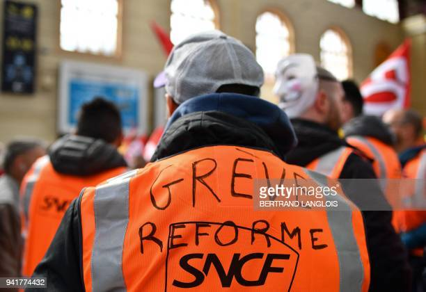 A rail worker wearing a SNCF high visibility vest with the words 'reform strike' takes part in a rally called by the French trade union the General...
