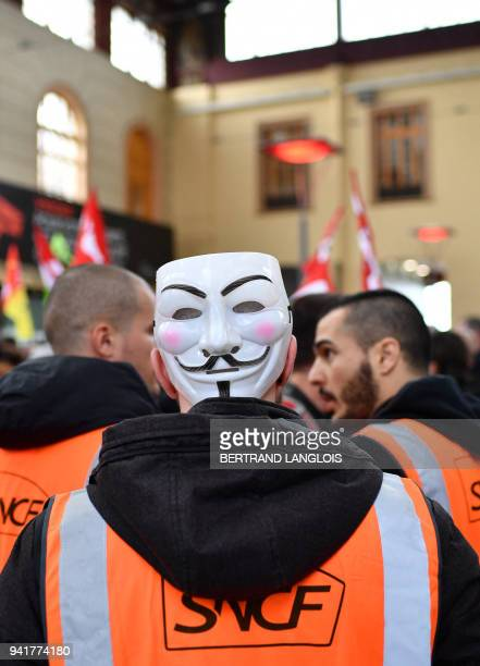 A rail worker wearing an Anonymous mask on the back of his head takes part in a rally called by the French trade union the General Confederation of...