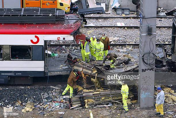 Rail workers cut a wagon of the train which exploded the day before at the Atocha train station 12 March 2004 in Madrid At least 198 people were...