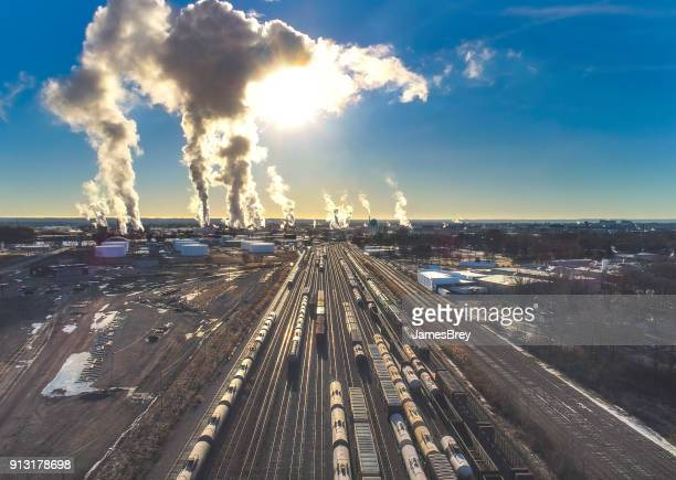 rail yard full of trains under industrial emissions, sunrise. - fumes stock photos and pictures