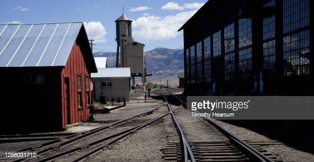 rail yard with related buildings and railroad tracks in foreground; mountains, blue sky with clouds beyond - timothy hearsum - fotografias e filmes do acervo