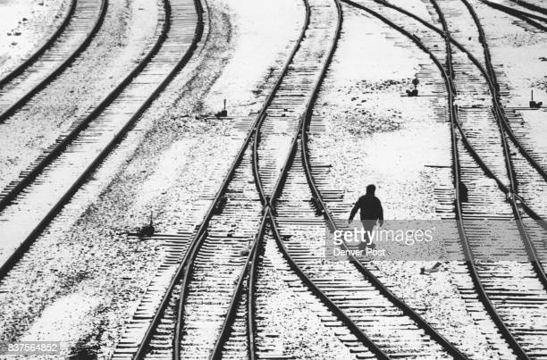 A rail yard worker walks across the snow covered rails at 23rd St Rail Yards snow remained on the ground in portions of the city today and cold Temp...