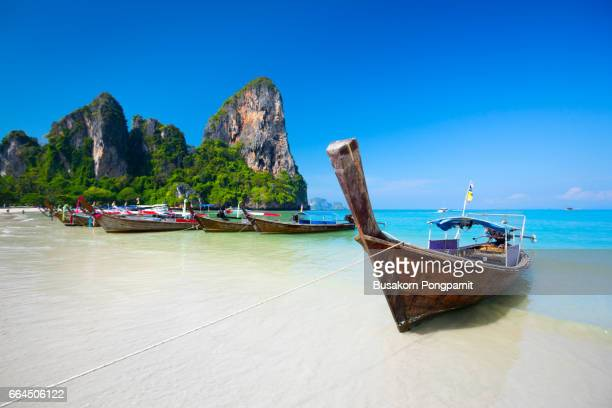 railay beach, tropical beach traditional long tail boat andaman sea thailand - phuket province stock pictures, royalty-free photos & images