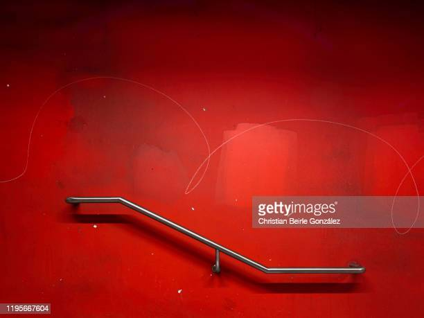 railing against a vibrant red wall with graffiti - christian beirle stock pictures, royalty-free photos & images
