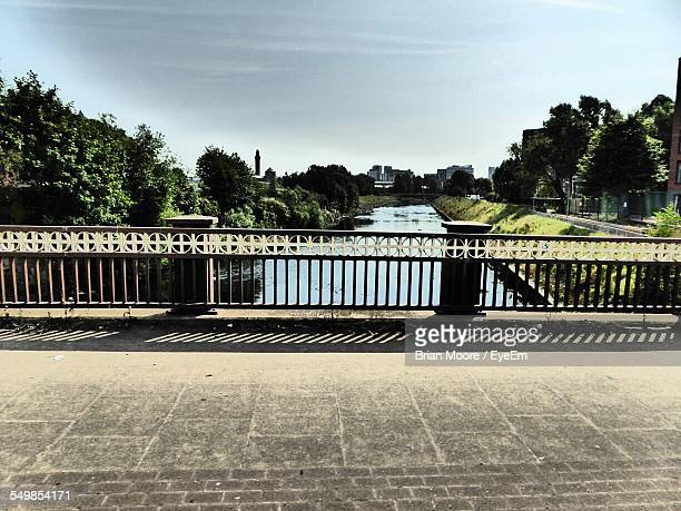 Railing Amidst Street And Canal On Sunny Day
