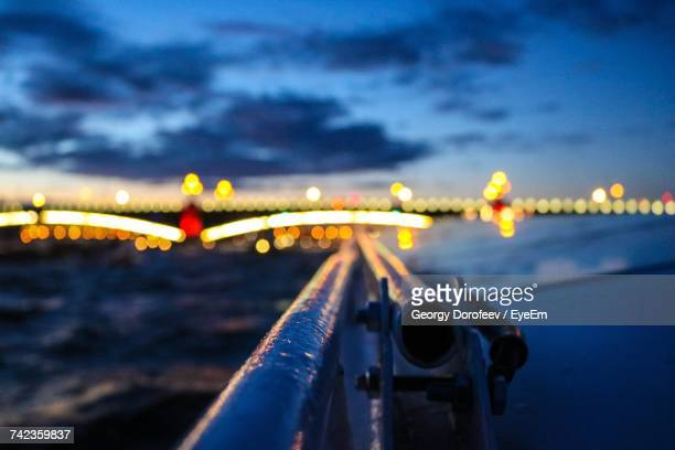railing by illuminated bridge over neva river against sky - neva river stock photos and pictures