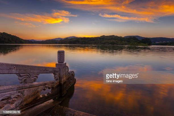 railing on lakeshore at sunset, nanjing, jiangsu province, china - image stock pictures, royalty-free photos & images