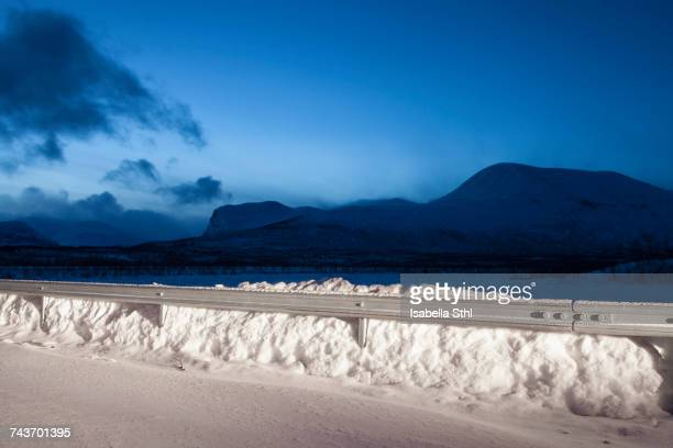 Railing on snow covered mountains against blue sky at night, Nikkaluokta, Sweden