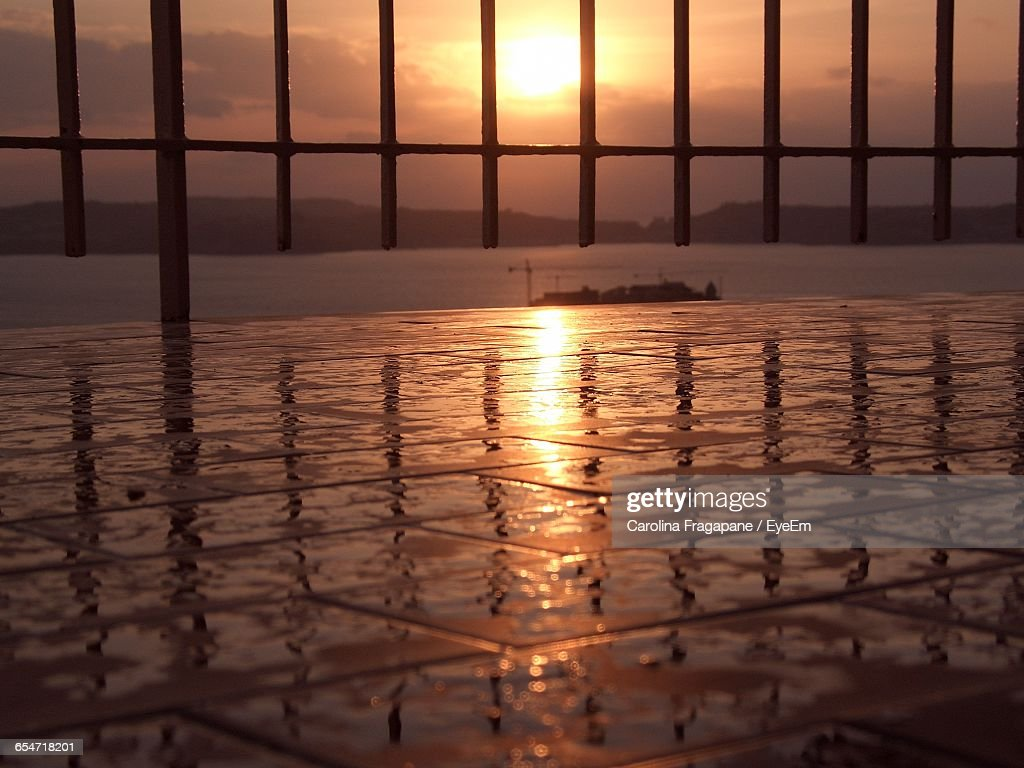 Railing On Wet Footpath By Sea During Sunset : Foto stock