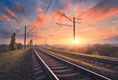 Railroad and beautiful sky at sunset. Industrial landscape with railway station, colorful blue sky with red clouds, trees and green grass, yellow sunlight in summer. Railway junction. Heavy industry