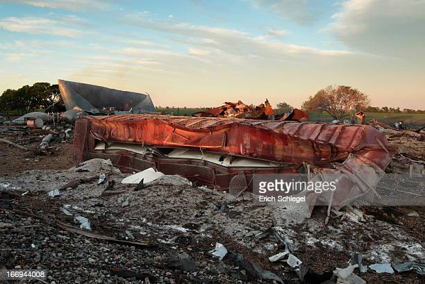A railroad boxcar filled with ammonium nitrate lays on its side near to the remains of the fertilizer plant that exploded yesterday afternoon on...