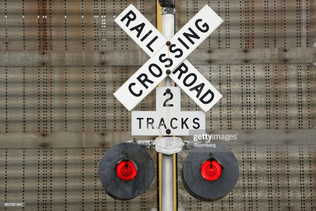 A railroad crossing gate stands along tracks owned by CSX