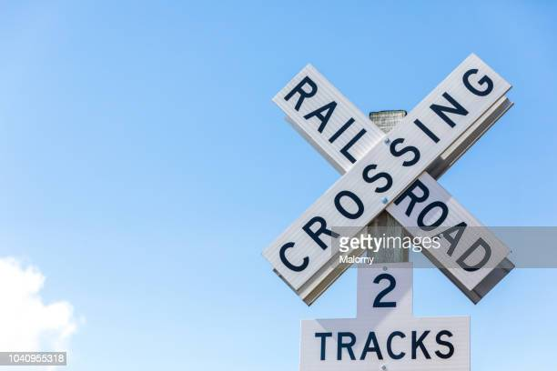 railroad crossing sign against clear blue sky. seattle, washington, usa. - railroad crossing stock pictures, royalty-free photos & images