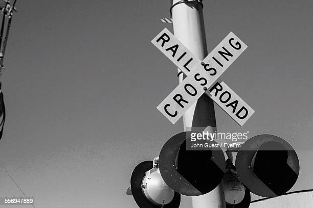 railroad crossing sign against clear sky - railroad crossing stock pictures, royalty-free photos & images