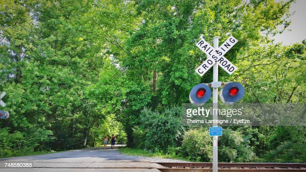 railroad crossing sign against trees - railroad crossing stock pictures, royalty-free photos & images