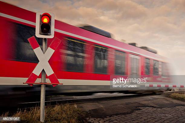 railroad crossing with train in motion blur - bernd schunack stock pictures, royalty-free photos & images