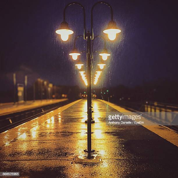Railroad Station Lit Up With Street Lights In Rain