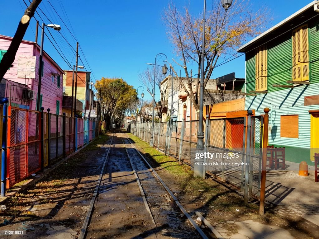 Railroad Track Amidst Bare Trees And Houses Against Sky : Stock Photo