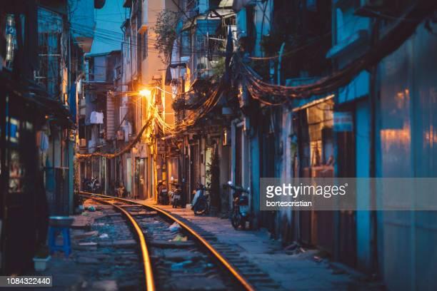 railroad track amidst buildings in city at night - bortes photos et images de collection