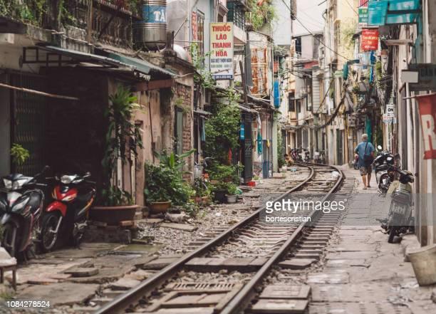 railroad track amidst buildings in city - bortes photos et images de collection
