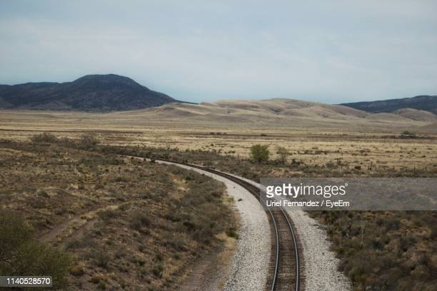 railroad track amidst landscape against sky - roswell stock pictures, royalty-free photos & images