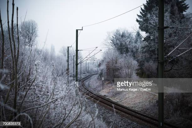 Railroad Track Amidst Trees Against Sky During Winter