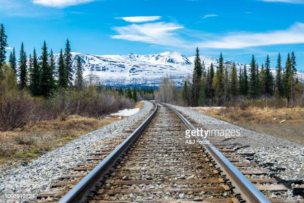 railroad track and mountain range - rocky mountains north america stock pictures, royalty-free photos & images