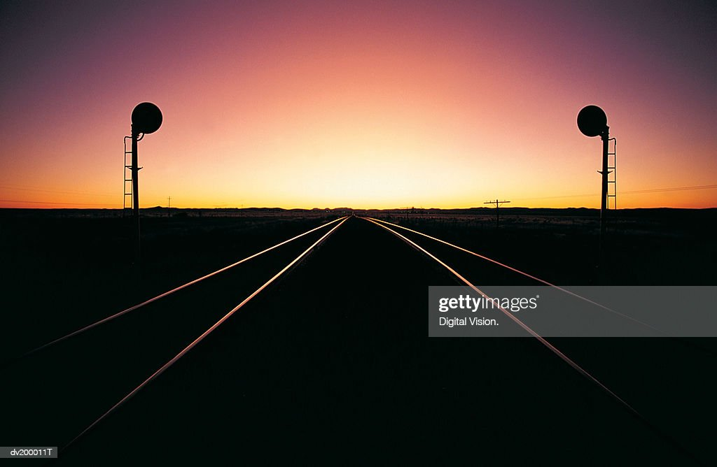 Railroad Track at Sunset Disappearing Into a Vanishing Point : Stock Photo