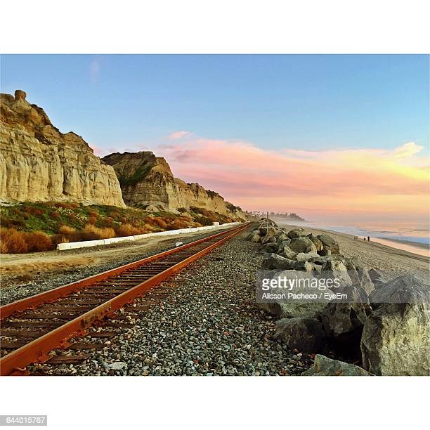 railroad track by beach against cloudy sky during sunset - alisson stock pictures, royalty-free photos & images