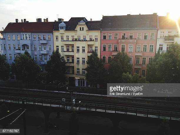 railroad track by building in city against sky - prenzlauer berg stock photos and pictures