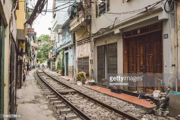 railroad track by building in city - bortes photos et images de collection
