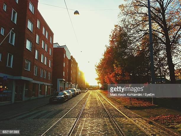 Railroad Track By Buildings Against Sky During Sunset