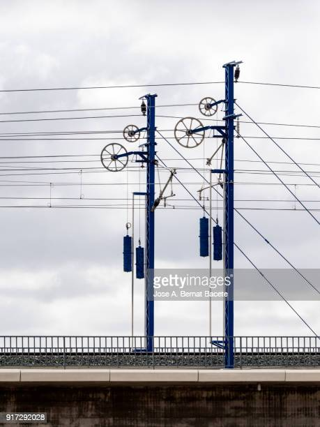 railroad track of the high-speed train ave on a bridge, with his electrical towers andcatenary. valencia, spain - metra train stock photos and pictures