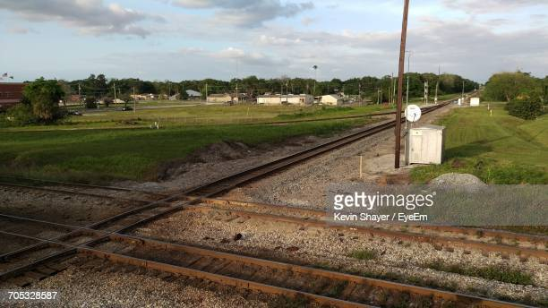 railroad track on field against cloudy sky - plant city stock pictures, royalty-free photos & images