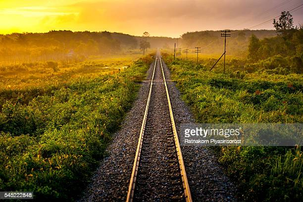 Railroad Track On Grassy Field At Morning