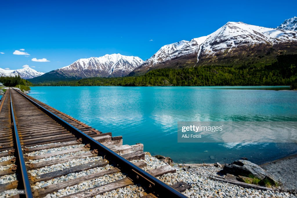 Railroad track with lake and mountain range : Stock Photo