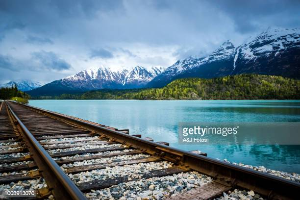 railroad track with lake and mountain range - chugach mountains stock pictures, royalty-free photos & images