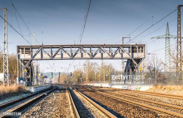 railroad tracks against clear sky - footbridge stock photos and pictures