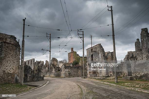 Railroad tracks amidst abandoned buildings in Oradour-sur-Glane against cloudy sky
