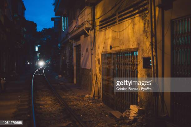 railroad tracks amidst buildings in city at dusk - bortes stock photos and pictures