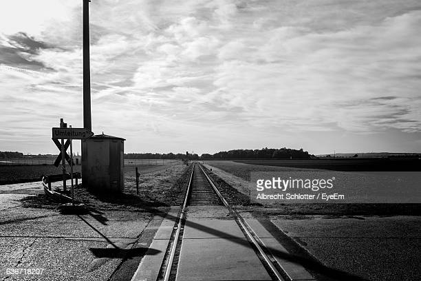 railroad tracks amidst field against cloudy sky - albrecht schlotter stock photos and pictures