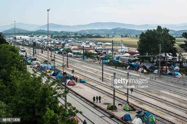 railroad tracks amidst refugee camp tents - refugee camp stock pictures, royalty-free photos & images