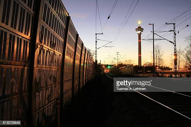 Railroad tracks and a sound barrier wall at dusk