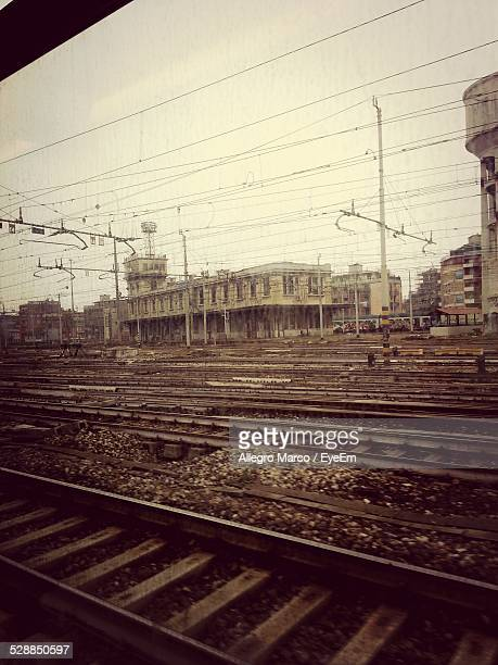 Railroad Tracks And Buildings Against Sky