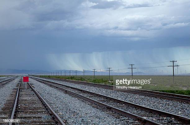 railroad tracks and power lines with storm beyond - timothy hearsum stock-fotos und bilder